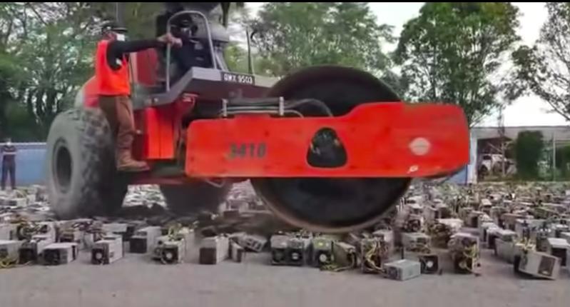 在網路瘋傳的影片顯示,馬來西亞警方出動一台蒸汽壓路機,將1,069台遭沒收的礦機通通碾碎。圖片擷取自影片