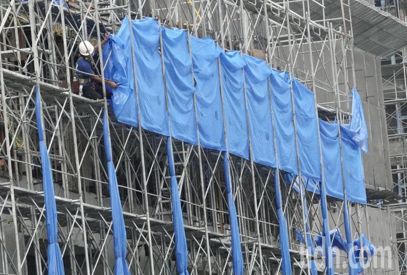 中度颱風烟花來襲,新北市下午下起間歇性陣雨,建築工地,工人紛紛將鷹架上的帆布收起來,避免強風吹襲,導致鷹架倒塌發生危險。記者黃義書/攝影