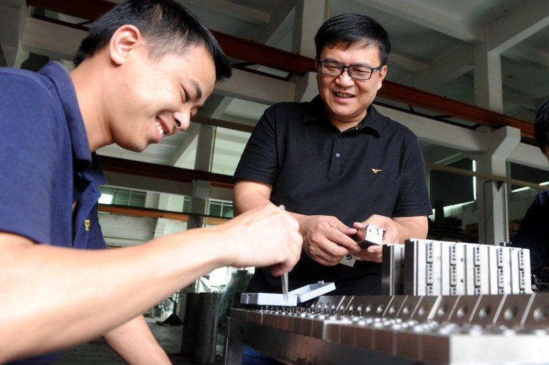 「台二代」陳勝裕(右)接手父親在漳州的事業,圖為他在車間與員工交流。(中新社)