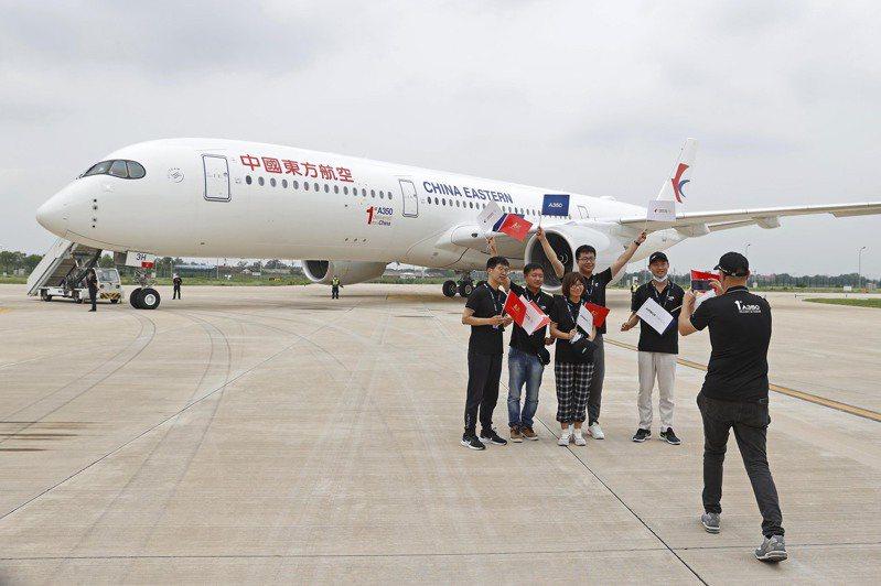7月21日,中國東方航空股份有限公司首次在天津接收空客交付的A350-900飛機。這是空客天津寬體飛機完成和交付中心向用戶交付的第一架A350飛機。圖為空客工作人員在飛機前合影留念。(中新社)