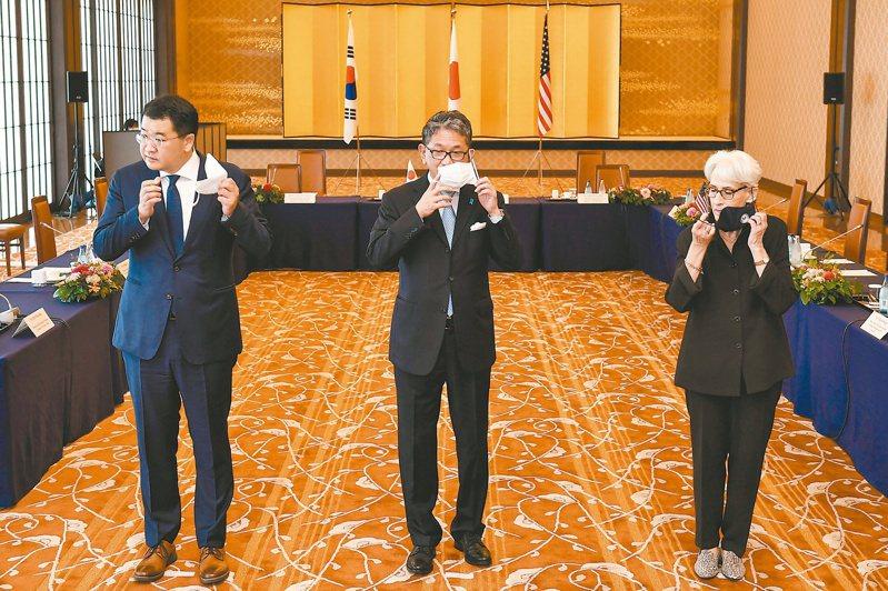 日本外務省事務次官森健良(中)與南韓外交部第一次官崔鍾建(左)、美國國務院副國務卿薛曼(右)二十一日在東京舉行三邊會談前,脫下口罩合影。(路透)