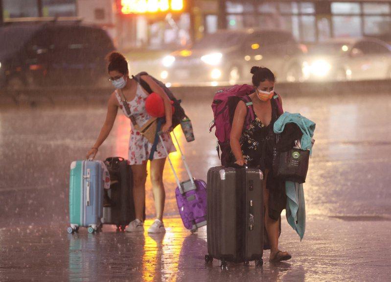中颱烟花持續增強,昨外圍環流已開始影響北台灣,雨勢愈晚愈大,台北街頭兩名外國女子下車後被大雨淋得措手不及。記者林澔一/攝影
