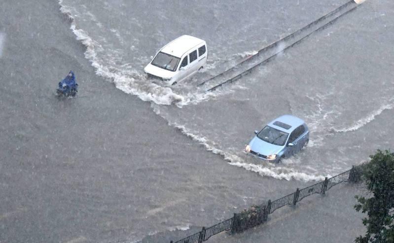 鄭州遭遇歷史極值暴雨,7月20日,車輛在鄭州街頭涉水前行。圖/取自新華社