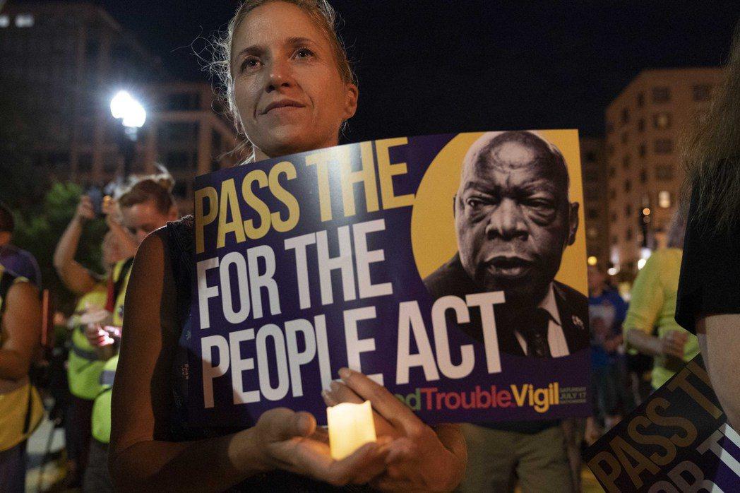 圖為今年7月美國民眾參加一場促進投票權集會,並手持美國前眾議院議員約翰・路易斯的海報。 圖/美聯社