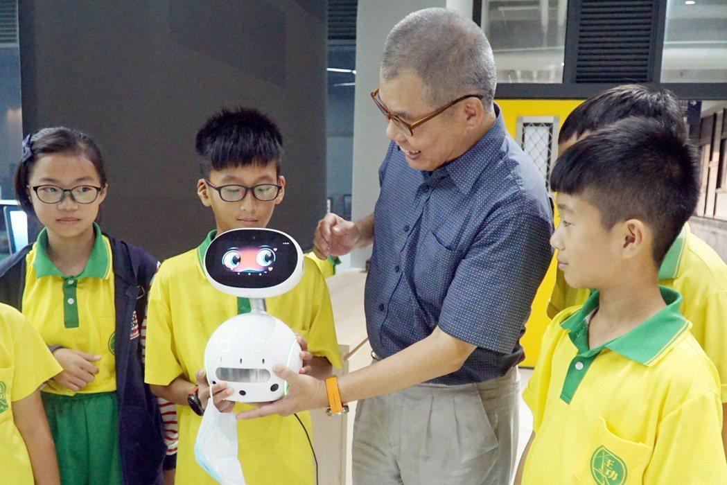 大葉大學電機系教授黃登淵(右二)向小朋友介紹機器人。