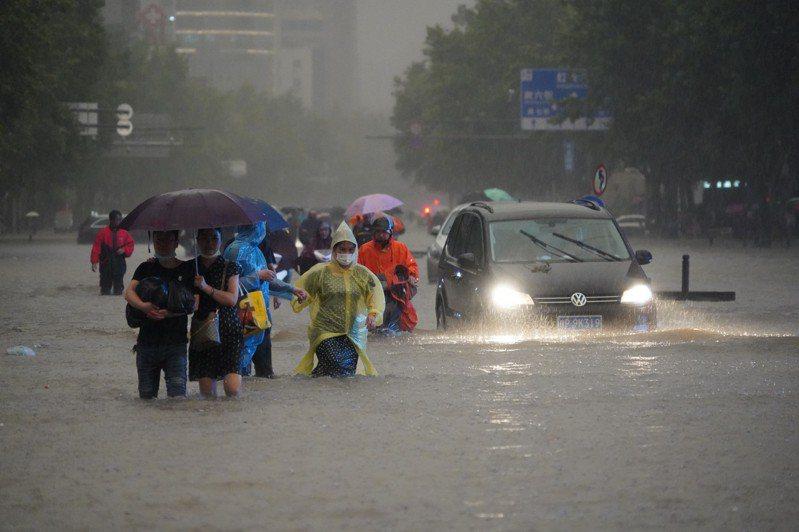 河南強降雨持續,鄭州市民暴雨中相互攙扶踏上回家路。(中新社)