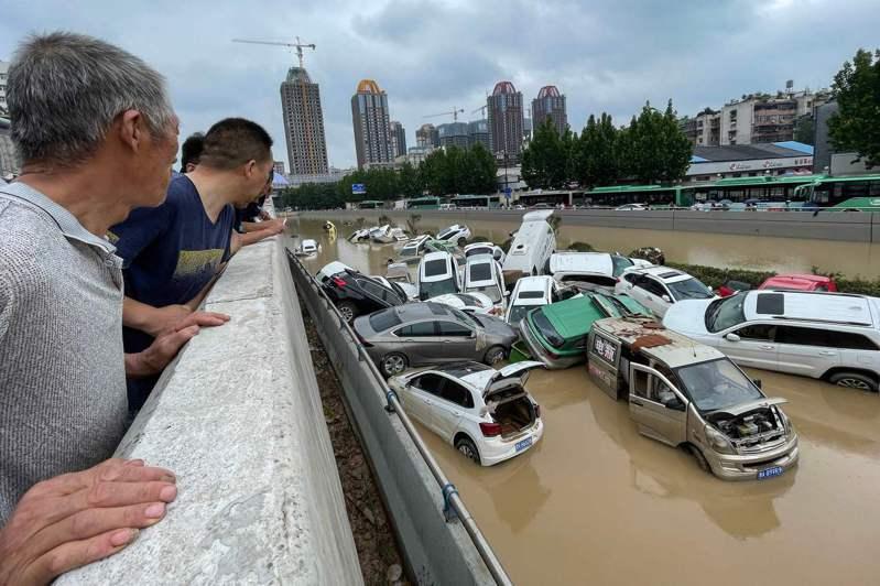河南鄭州嚴重淹水,民眾廿一日圍觀一堆泡水車。(法新社)