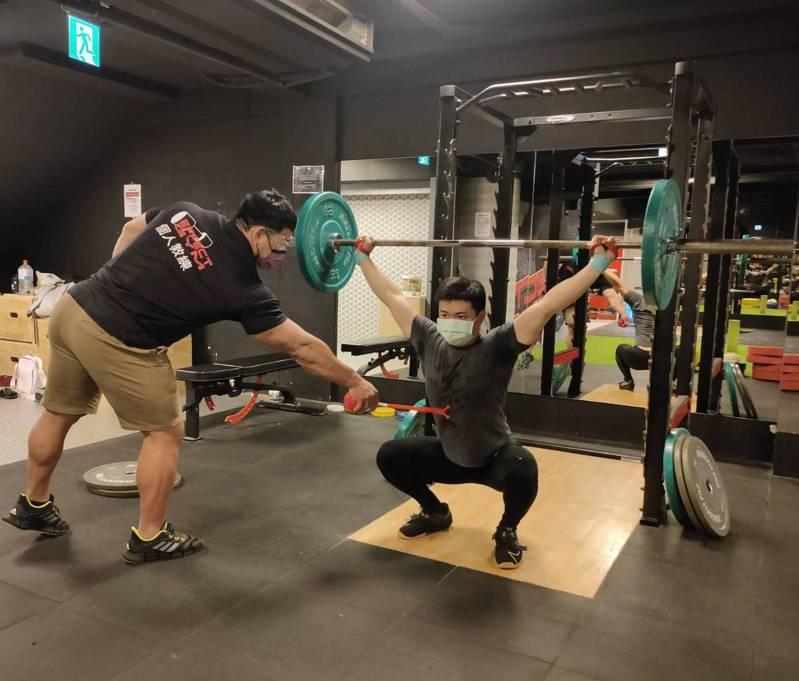 健身教練石天鴻(左)以愛的小手指導學員林漢永(右),避免肢體碰觸。記者林佩均/攝影