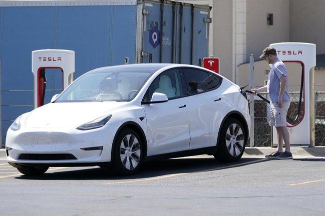 特斯拉車主正在為愛車充電。  美聯社