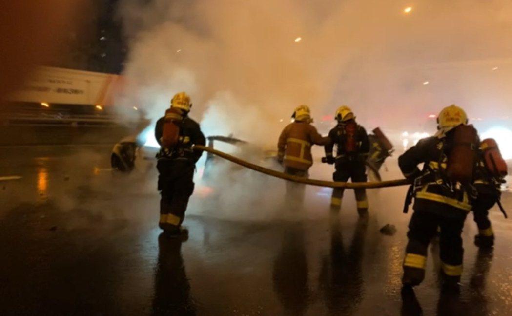 BMW雙門轎跑車打滑自撞護欄起火,消防隊趕抵滅火。記者林昭彰/翻攝