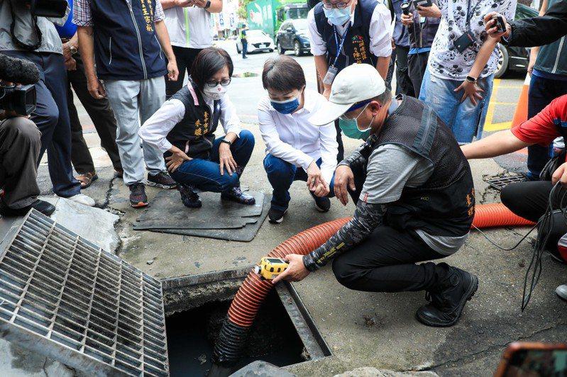 中颱烟花來襲,台中市長盧秀燕(中)昨天視察道路側溝清淤作業,以科技偵測發現大量「油塊」卡在溝邊。記者喻文玟/攝影
