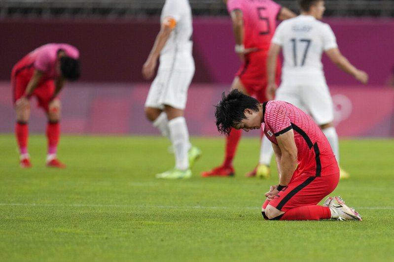 南韓暴冷不敵紐西蘭,球員失望跪坐在草地上。 美聯社