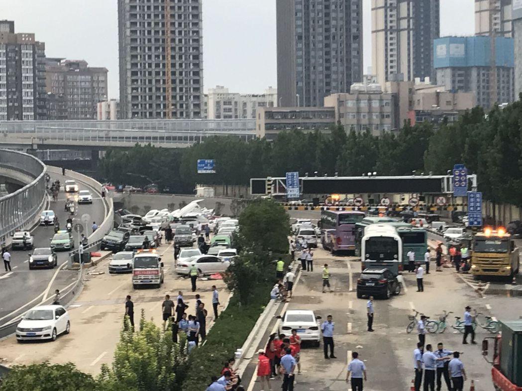 圖為京廣北路隧道口22日下午景象,露出水面的車輛疊羅漢般堆疊在路面上。(取自《新...