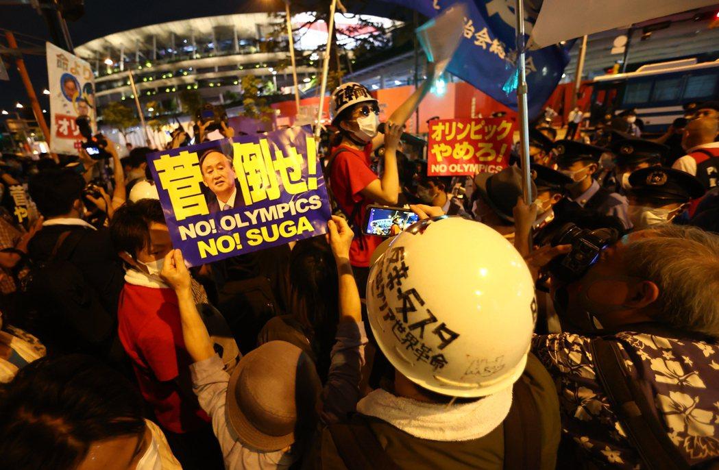 數百人23日聚在東京奧運開幕式會場國立競技場外,高喊「停辦奧運」等口號。(路透)
