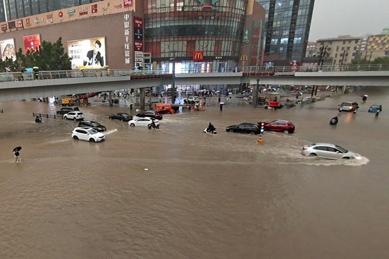 河南多地連日暴雨成災,已有56人遇難、5人失蹤,救援工作進行中。圖為20日時的河南街頭,人車都泡在水中情景。美聯社