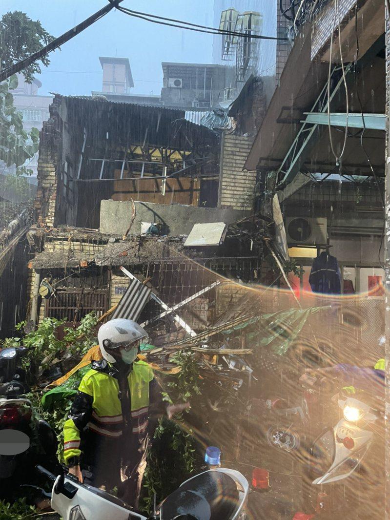 三重中央北路122巷內,有廢棄民宅2樓外牆及路樹倒下,壓毀停在路邊機車。圖/新北消防局提供