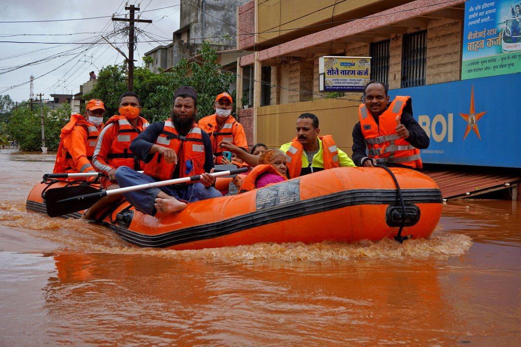 印度國家災害反應部隊24划著橡皮艇,載民眾脫離洪水災區。(路透)