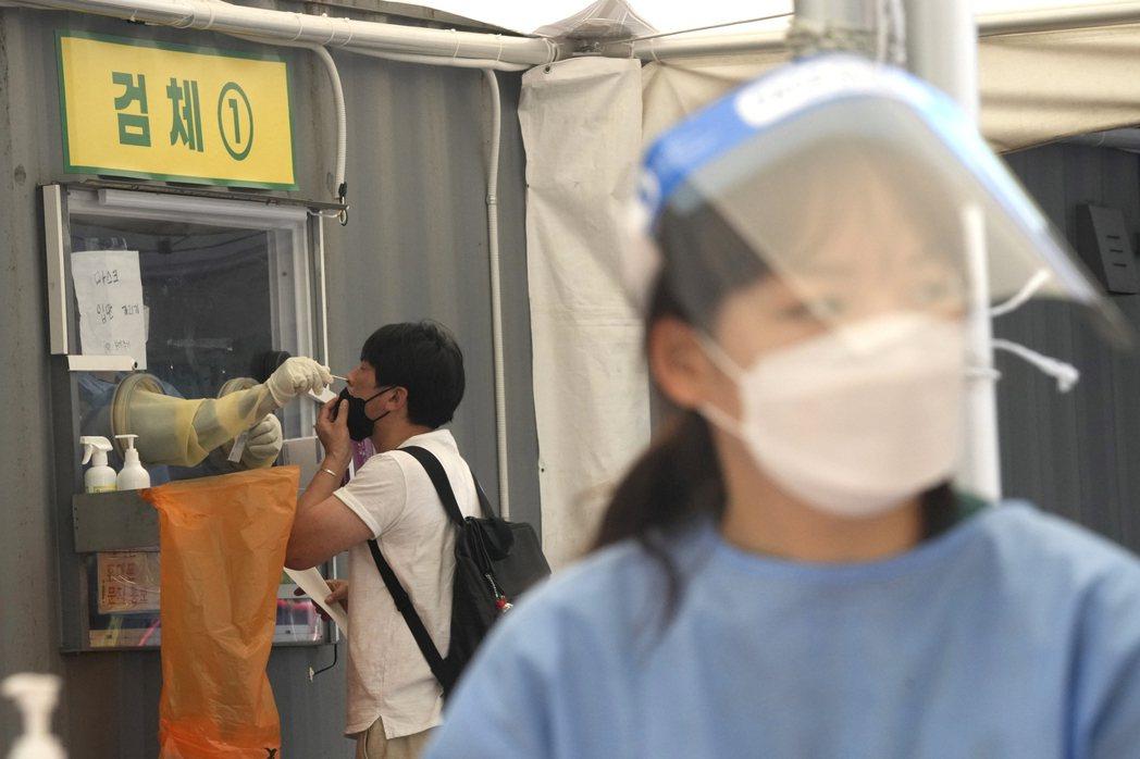 南韓疫情持續惡化,非首都圈自26日升至三級警戒,圖為首爾市內一處臨時篩檢站。美聯...