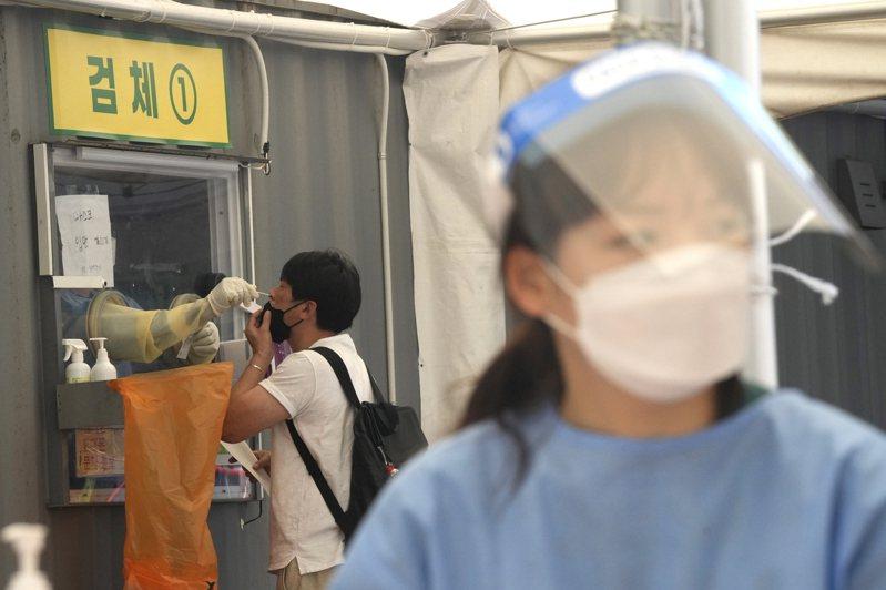 南韓疫情持續惡化,非首都圈自26日升至三級警戒,圖為首爾市內一處臨時篩檢站。美聯社