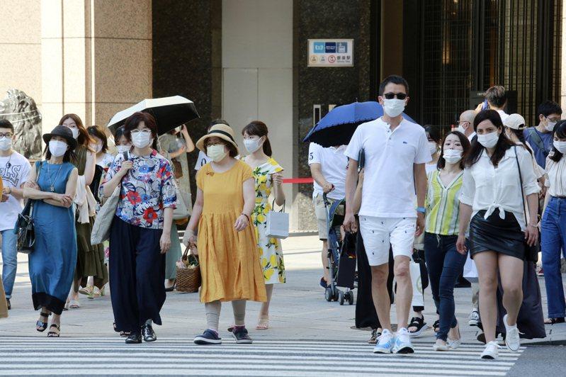 日本東京戴口罩民眾24日經過街頭。美聯社