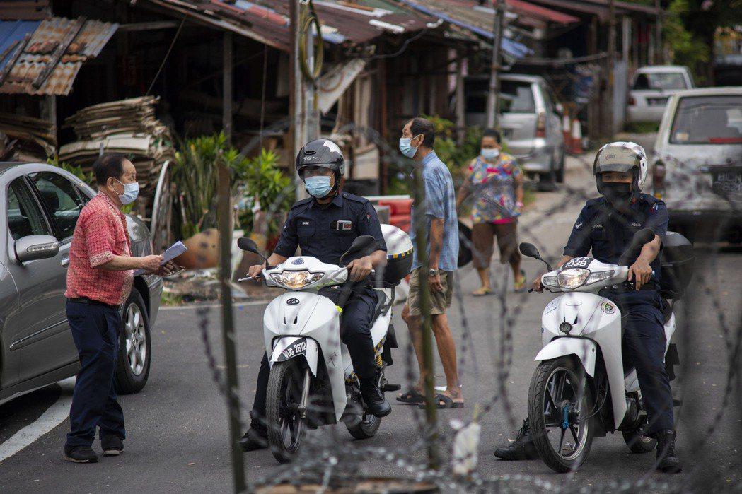 馬來西亞日增病例連三天創下新高,圖為吉隆坡警方24日騎車在加強防疫地區內巡邏。新...