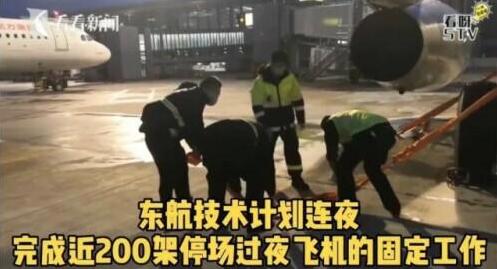 東航技術人員24日晚連夜用工具將飛機固定,以免飛機被強颱煙花吹襲,造成損失。(網...