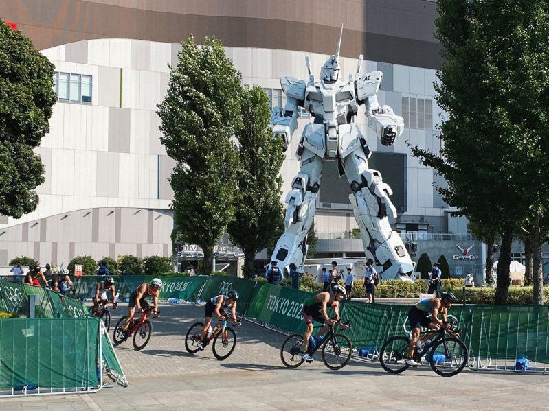 鐵人三項項目中,選手們騎著腳踏車,通過台場地標「獨角獸鋼彈」。圖擷取自twitter