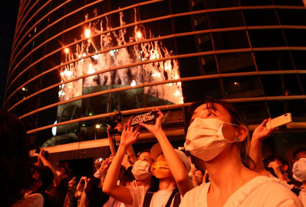 「開幕式預算165億日元都花去哪裡了?」圖為開幕式當天晚上,聚集在場外的民眾。本...