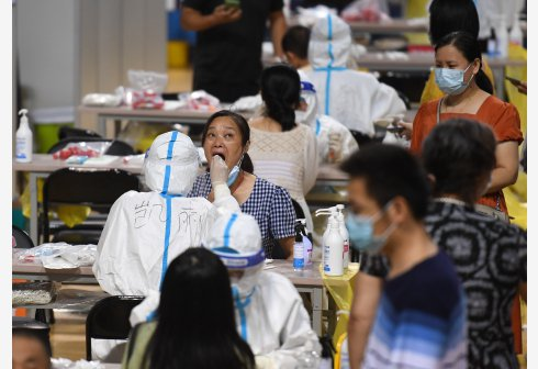 7月25日,在南京市鼓樓區五台山體育中心體育館內,醫務人員為市民進行核酸檢測取樣...
