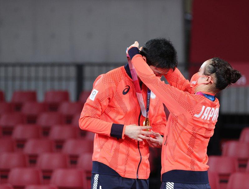 日本隊水谷隼(左)與伊藤美誠拿下桌球混雙金牌,兩人互掛獎牌,相當溫馨。新華社