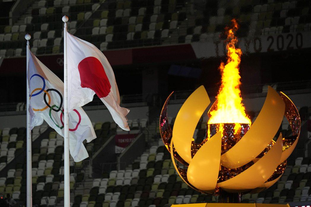 本次東京奧運顯然不只是喚醒「那個美好的六〇年代」的記憶而已,而是讓日本人了解自己深處在當代世界戰略的十字路口。圖為國際奧會、日本國旗與2020年東京奧運聖火台。 圖/美聯社