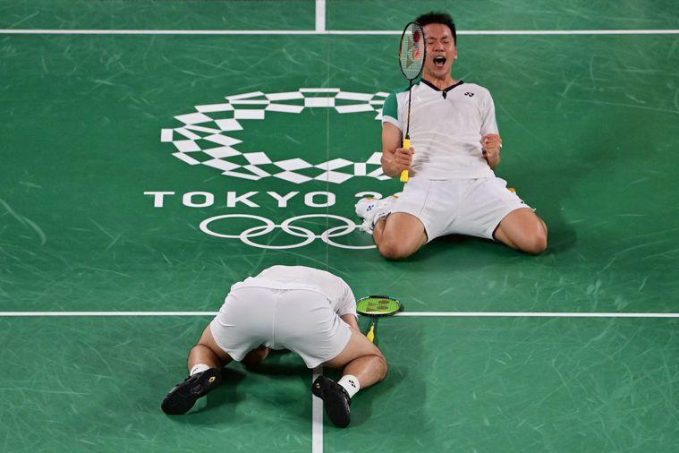 我國羽球男雙組合李洋(後)、王齊麟獲勝時的慶祝姿勢神似一正一反的「聖筊」,成為熱...