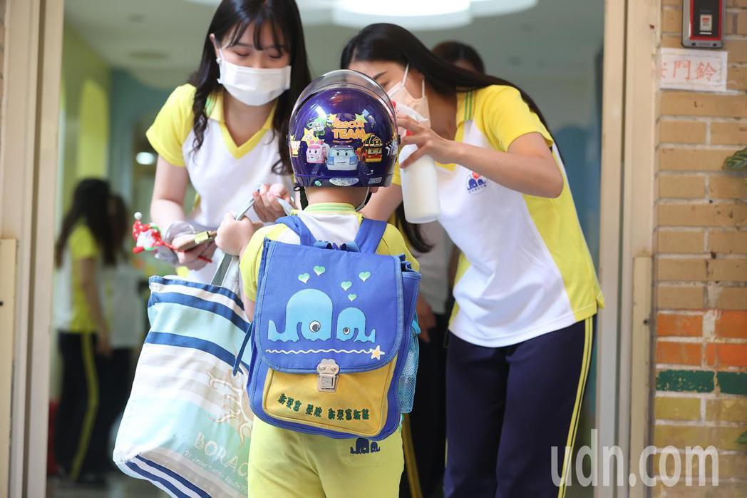 今起降級,幼兒園復課,孩子提著隨身物品前來上課。記者葉信菉/攝影