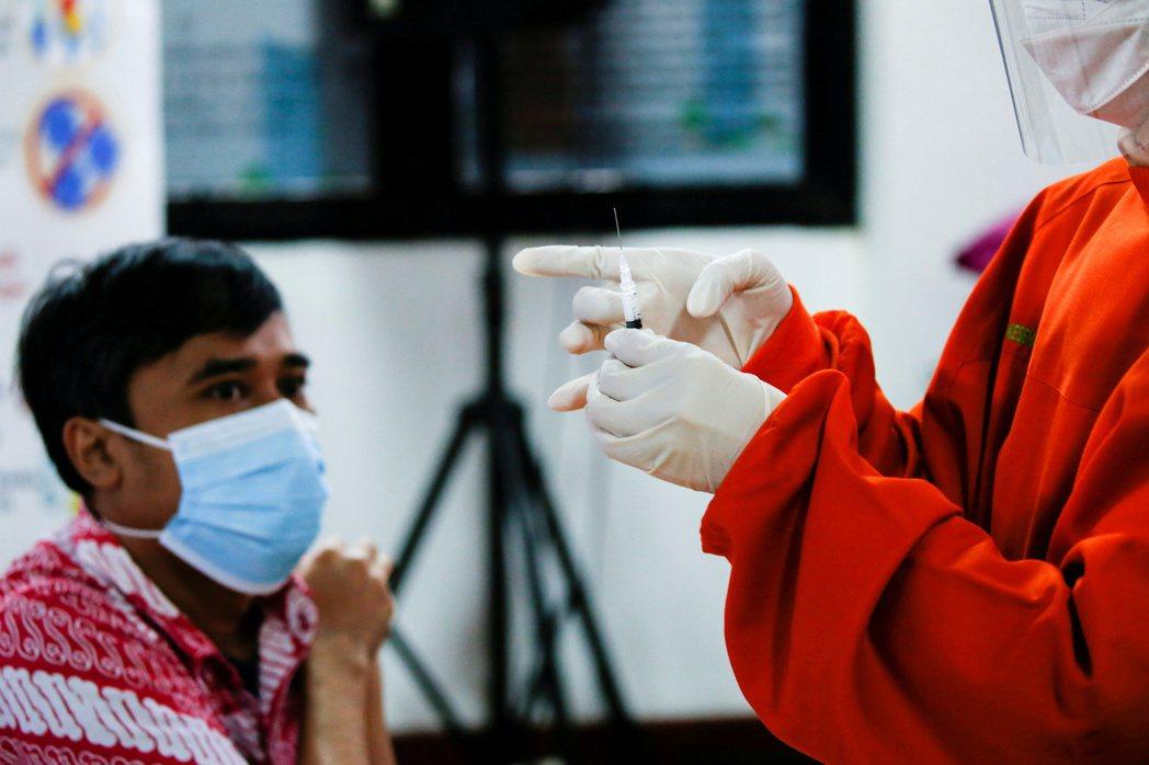 印尼政府正考慮實施第三劑加強針計畫,圖為一位準備接種科興疫苗的印尼民眾。路透