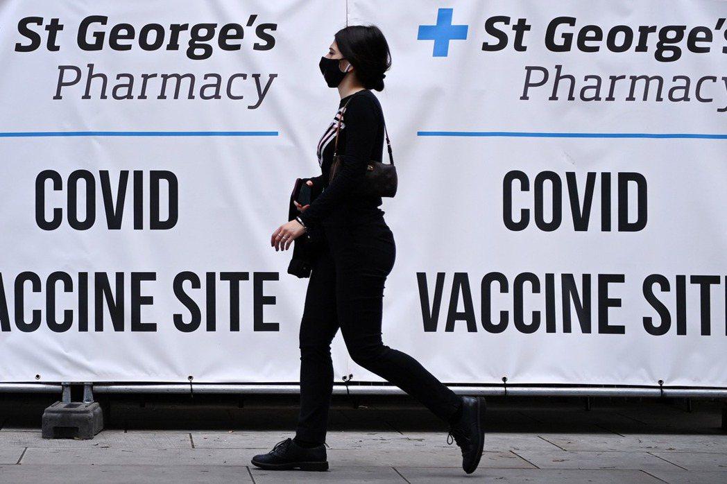 圖為一名女性行經英國一處新冠疫苗接種站的標示布條。 圖/歐新社