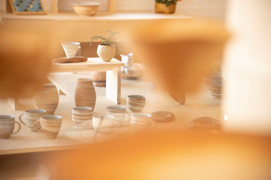 混合台南六甲磚土與瓷土的比例調配出漸層色調,組構出如等高線的地層線條,盤中圖樣像...