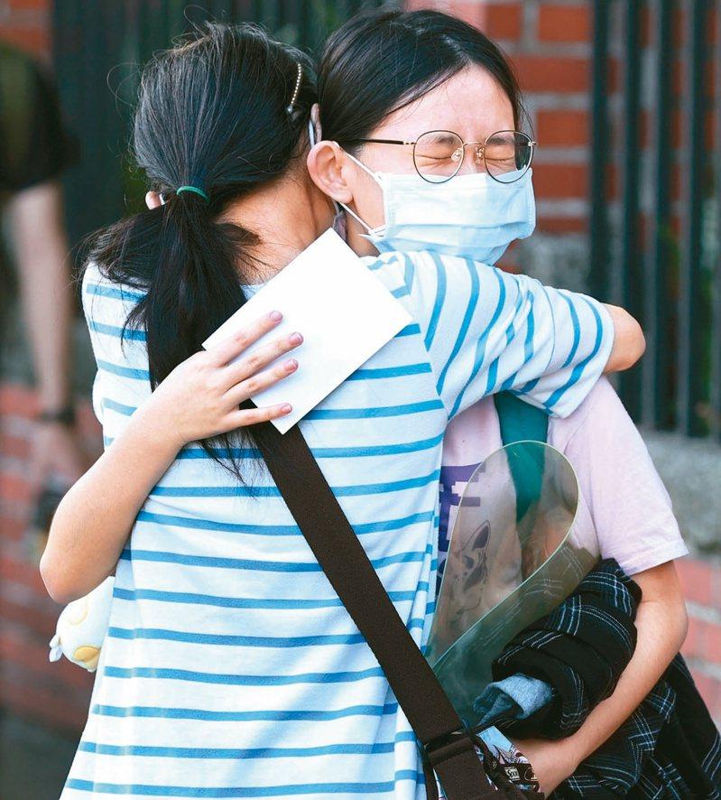 兩度延期的末代指考昨天登場,因防疫規範,不開放家長與親友陪考。一位母親在考場外擁抱鼓勵女兒。記者侯永全/攝影