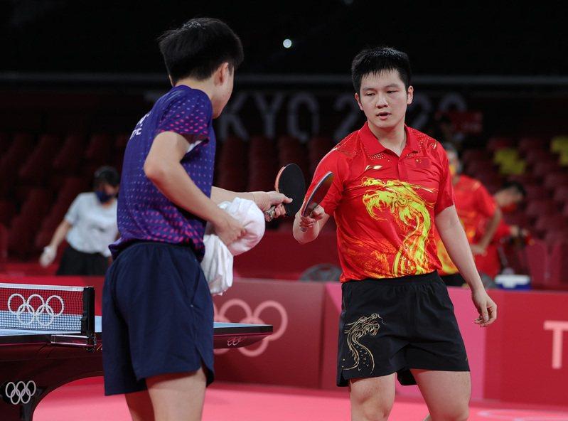 球王樊振東(右)打敗台灣好手林昀儒,中國球評稱以暴制暴。 路透