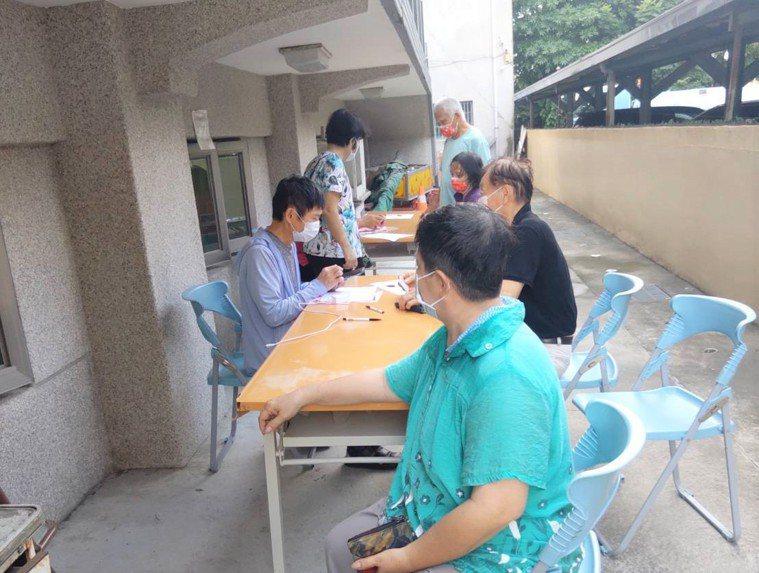 台南市麻豆區東角里有志工協助長輩上網登記及預約1922。圖/東角里長提供
