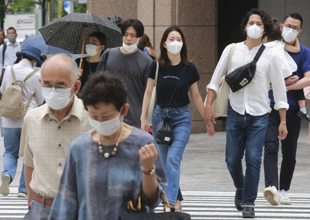 日本東京戴口罩民眾27日經過街頭。美聯社