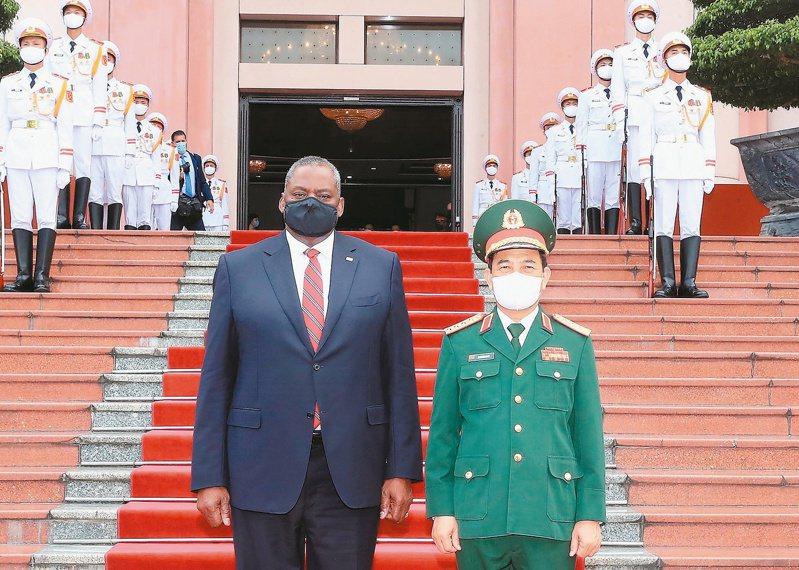 美防長奧斯丁(左)廿九日造訪河內,受到越南國防部長潘文江(右)歡迎。(歐新社)