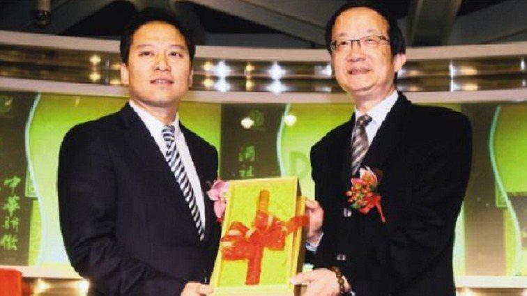 時任證交所總經理許仁壽(右),於2011年3月9日贈送簽名鼓棒給時任杜康控股執行...
