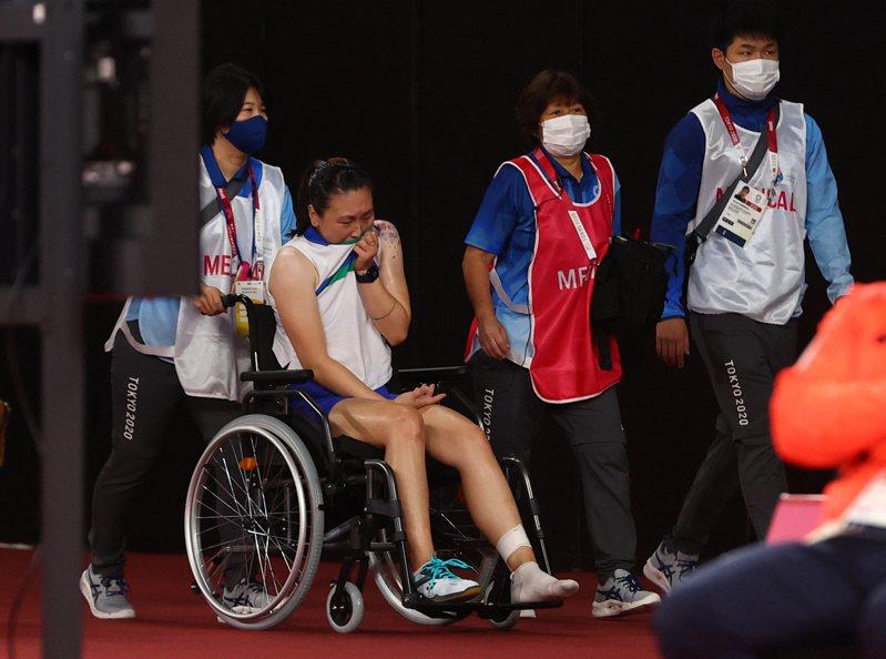 美國羽毛球球手張蓓雯擊球後落地時拐腳倒地,不慎觸傷左腳足踝,無奈退賽以輪椅代步離開球場。 路透社