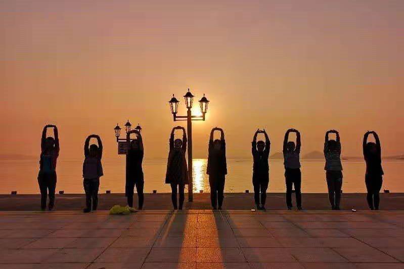 與夕陽相伴,微慢跑後一起拉筋伸展。 圖/章旭輝 提供