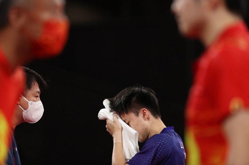 台灣桌球好手林昀儒(後)29日下午在東京奧運桌球男子單打4強戰遇上中國頭號種子樊振東,雙方激戰7局,彼此一路緊咬,終場林昀儒以3比4飲恨落敗。圖為林昀儒在場邊擦拭汗水。 圖/中央社提供