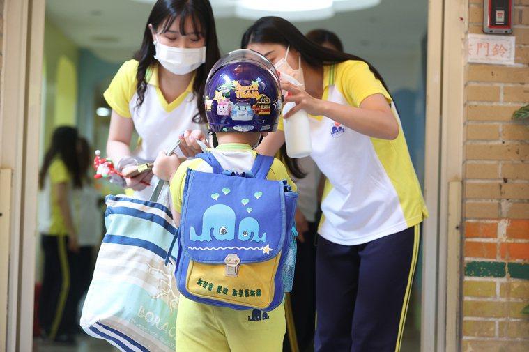近期幼兒園、托嬰中心、補習班等教保機構陸續解封,孩子提著隨身物品前來上課。記者葉...