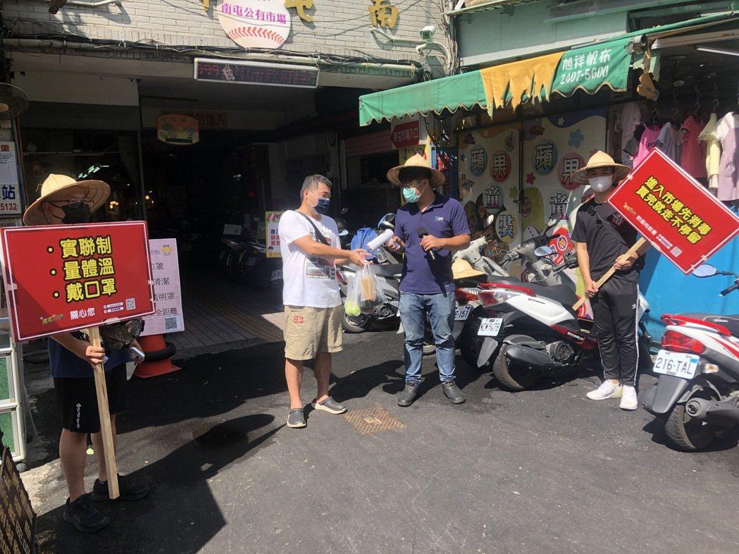 4名斗笠熱血青年合體組成「市場防疫宣導員」,在南屯市場入口幫忙買菜族噴酒精、舉牌...