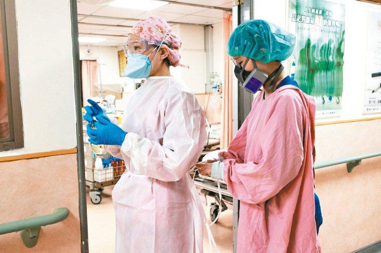 急診室內醫護人員互相幫忙穿著防護衣。記者季相儒/攝影