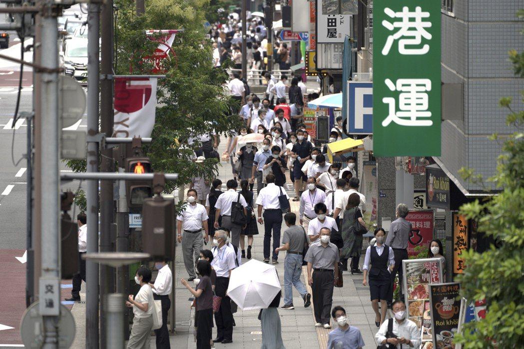 日本東京民眾26日午餐時間經過繁忙街道。美聯社