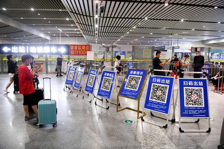 大陸各地疫情防控近日紛紛升級,圖為旅客在湖南長沙高鐵南站掃健康碼。中新社
